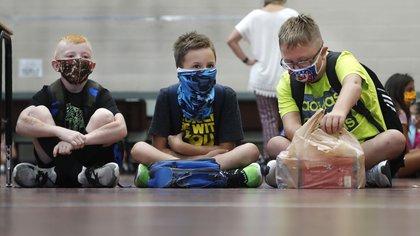 Tres estudiantes de primaria portando mascarillas para evitar la propagación de COVID19 esperan a que comiencen las clases en Godley, Texas, el miércoles 5 de agosto de 2020. Tres distritos escolares rurales en el condado de Johnson estuvieron entre los primeros en Texas en regresar a clases presenciales. (FotoAP/LM Otero)