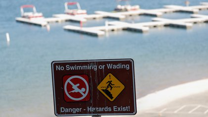 """A """"No swimming"""" sign is pictured as the search for missing actor Naya Rivera continues on Lake Piru in California, U.S., July 9, 2020. REUTERS/Mario Anzuoni"""