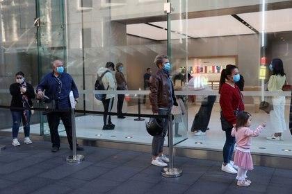 FOTO DE ARCHIVO: Varias personas con mascarillas observan las normas de distanciamiento social mientras esperan para entrar en una tienda de Apple en Sídney, Australia, el 1 de julio de 2020. REUTERS/Loren Elliott