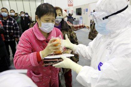 Una paciente recibe su almuerzo en el Centro de Convenciones de Wuhan, el 15 de febrero de 2020 (China Daily via REUTERS)