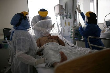 Un médico y dos enfermeras tratan a un paciente aquejado de coronavirus en la UCI del hospital El Tunal en Bogotá, Colombia. 12 junio 2020. REUTERS/Luis González