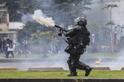 Un policía dispara gases lacrimógenos a manifestantes en Bogotá, Colombia, el jueves 21 de noviembre de 2019. (AP Foto / Ivan Valencia)