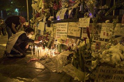 Una mujer enciende una vela en un altar improvisado en memoria de las víctimas de las protestas recientes ante el edificio del Congreso, mientras esperan a saber quién será el próximo presidente del país (AP Foto/Rodrigo Abd)