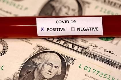 Ilustración fotográfica que muestra un billete de dólar junto a un tubo de muestra para detectar el coronavirus. 1 marzo 2020. REUTERS/Dado Ruvic