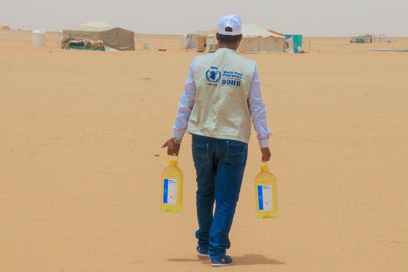 05-08-2021 Un trabajador lleva botellas de aceite vegetal del PMA para distribuirlas entre los desplazados internos en un campamento de YemenPOLITICA © PMA / HANI SALEH