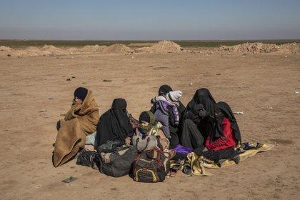 La mayoría de las mujeres y niños que huyen del territorio del Estado Islámico terminan en campamentos en el este de Siria. Un grupo de ellos esperaba en febrero a que las fuerzas kurdas los chequearan. (Ivor Prickett/The New York Times)