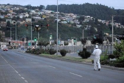 Trabajadores usan un drone para esparcir desinfectante en Talcahuano (Reuters)