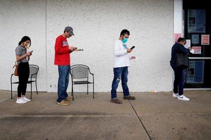 Varias personas hacen cola para solicitar una prestación por desempleo en la Oficina de Empleo de Arkansas en Fayetteville, Arkansas, Estados Unidos, el 6 de abril de 2020. REUTERS/Nick Oxford