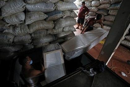 Los trabajadores llevan ataúdes, que llegaron del estado de Santa Catarina al Puerto de Manaus y fueron comprados por las funerarias, en medio del brote de la enfermedad coronavirus (COVID-19), en Manaos,
