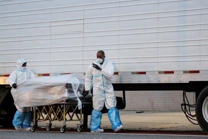 Empleados funerarios completamente protegidos trasladan un cuerpo de una víctima de coronavirus en el barrio de Brooklyn de la ciudad de Nueva York (Reuters)