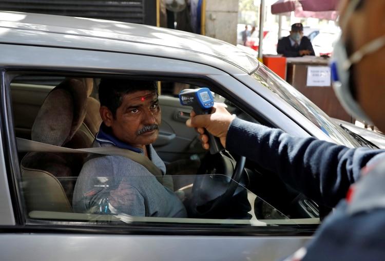 Una persona es revisada en un control de temperatura al ingresar a un edificio de oficinas en Nueva Delhi, India (Reuters)
