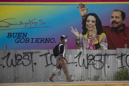 Un hombre camina al lado de una valla publicitaria en Managua donde aparecen el presidente de Nicaragua, Daniel Ortega, y su esposa, Rosario Murillo, la vicepresidenta, el 20 de mayo de 2020. (Inti Ocon/The New York Times)