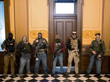 Un grupo de milicianos sin afiliación política de Michigan se encuentra frente a la oficina del gobernador después de que los manifestantes ocuparan el edificio del capitolio estatal durante una votación para aprobar la extensión de la declaración de emergencia/orden de permanencia en el hogar de la gobernadora Gretchen Whitmer debido al brote de coronavirus (REUTERS/Seth Herald)