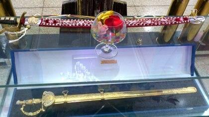 """Un copa de cristal con caramelos, pétalos y miel puesta arriba de la espada del libertado Simón Bolívar para """"atraer y endulzar a su espíritu"""". (Foto: David Placer)"""