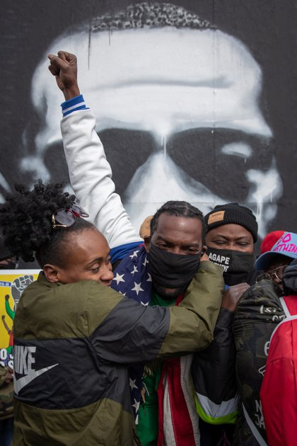 Local residents Mileesha Smith, Michael Wilson and Alfonzo Williams hug after the verdict in the trial of former Minneapolis police officer Derek Chauvin, convicted of George Floyd's death, at George Floyd Square in Minneapolis, Minnesota (Reuters)
