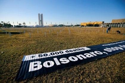 """""""Más de 50.000 muertes. Bolsonaro pare de negar"""", dicen los carteles colocados junto a las cruces (REUTERS/Adriano Machado)"""