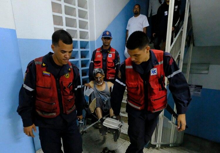 Un paciente en silla de ruedas es cargado por las escaleras ante la falta de funcionamiento de los ascensores(AFP)