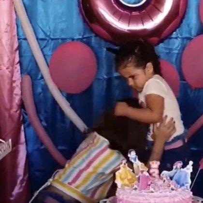 La niña de tres años está tirando del cabello a su hermana de seis años después de apagar las velas de su pastel de cumpleaños.