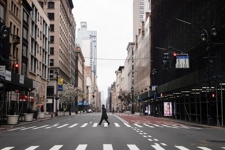 Un hombre cruza la icónica Quinta Avenida en Manhattan, que se encuentra prácticamente vacía. Foto: REUTERS/Mike Segar