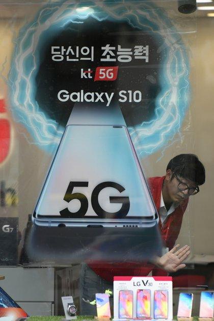Un empleado prepara un anuncio para el servicio de redes móviles 5G de KT en una tienda de telecomunicaciones en Seúl. (AFP)