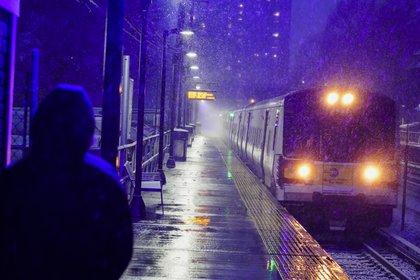 Una mujer espera un tren de Long Island Rail Road en el distrito de Queens de Nueva York mientras cae nieve al inicio de la tormenta de nieve  (AP Photo / Frank Franklin II).