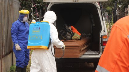 Trabajadores gubernamentales proceden a sacar de un vehículo un féretro con una víctima de covid-19 para su posterior entierro el 8 de agosto de 2020, en el cementerio de San Cristóbal, estado Táchira (Venezuela). EFE/ Johnny Parra