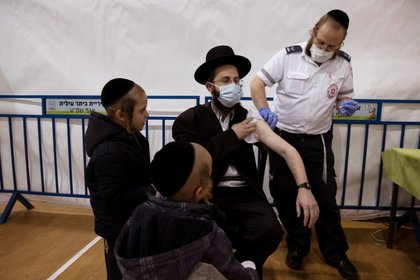 An ultra-Orthodox Jewish man receives a vaccination against the coronavirus disease (COVID-19) at a temporary vaccination centre in the Jewish settlement of Beitar Illit, in the Israeli-occupied West Bank February 16, 2021. Picture taken February 16, 2021. REUTERS/Ronen Zvulun