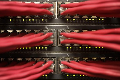 Rows of colored high end data cables are seen feeding into racks of computer servers inside a comms room at an office in London, U.K., on Tuesday, Dec. 23, 2014. Vodafone Group Plc will ask telecommunications regulator Ofcom to guarantee that U.K. wireless carriers, which rely on BT's fiber network to transmit voice and data traffic across the country, are treated fairly when BT sets prices and connects their broadcasting towers. Photographer: Bloomberg/Bloomberg