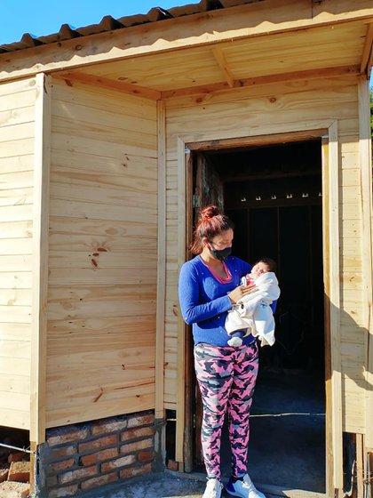 Gimena con su bebé de dos meses en brazos en la puerta de la casa que le costearon sus vecinos con la venta de una rifa.