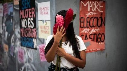 """Jessika, de 21 años, que atravesó un embarazo en soledad, frente a una instalación con consignas feministas en Caracas. Peso a que Hugo Chávez y Nicolás Maduro se proclamaron """"feministas"""", los derechos reprodujctivos de planificación del embarazo dieron un gran paso atrás bajo el régimen chavista."""