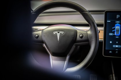 A sits on the steering wheel of a Tesla Inc. Model 3 electric vehicle in the Tesla store in Barcelona, Spain, on Thursday, July 11, 2019. Tesla is poised to increase production at its California car plant and is back in hiring mode, according to an internal email sent days after the company wrapped up a record quarter of deliveries.
