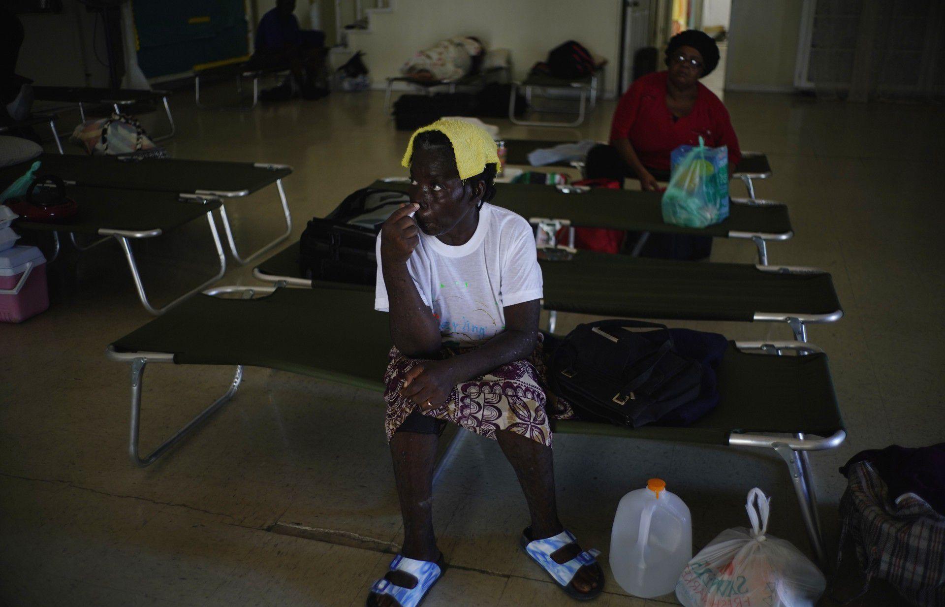 Dos mujeres sentadas en catres dentro de una iglesia empleada como refugio para los vecinos, que esperarán allí a que pase el huracán Dorian, en Freeport, Gran Bahama (AP Foto/Ramón Espinosa)