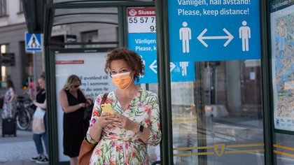 A woman wearing a face mask is seen in a bus stop next to an information sign asking people to keep social distance due to the outbreak of coronavirus disease (COVID-19), in Stockholm, Sweden June 26, 2020. Stina Stjernkvist/ TT News Agency/via REUTERS      ATTENTION EDITORS - THIS IMAGE WAS PROVIDED BY A THIRD PARTY. SWEDEN OUT. NO COMMERCIAL OR EDITORIAL SALES IN SWEDEN.
