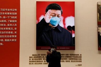 Un visitante se encuentra cerca de una imagen del presidente chino Xi Jinping durante una exposición sobre la lucha contra la pandemia del coronavirus (COVID-19), en el Centro de Convenciones de Wuhan Parlor que anteriormente sirvió como hospital improvisado para los pacientes de COVID-19 en Wuhan, provincia de Hubei, China, 31 de diciembre de 2020. REUTERS/Tingshu Wang