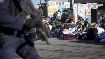 La policía nacional se cubre cuando se escuchan disparos al final de la ceremonia. Al menos tres personas resultaron heridas en el acto oficial (AP Photo/Dieu Nalio Chery)