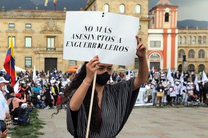 Una modelo desfila ropa elaborada por desmovilizados de las FARC y víctimas del conflicto mientras sostiene un cartel hoy, martes en la Plaza de Bolívar, de Bogotá. EFE/ Carlos Ortega