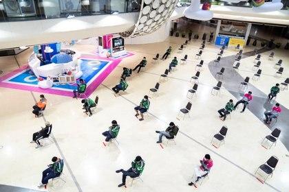 Empleados de delivery esperan pedidos, sentados y manteniendo la distancia social, en un shopping de Bangkok, en Tailandia (REUTERS/Athit Perawongmetha)