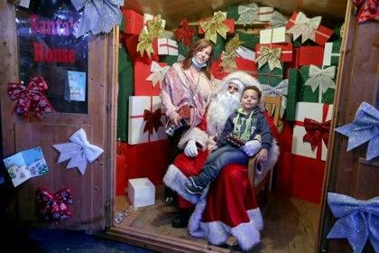 Un niño toma una foto con un hombre vestido de Papá Noel en Beirut, Líbano (REUTERS/Mohamed Azakir)