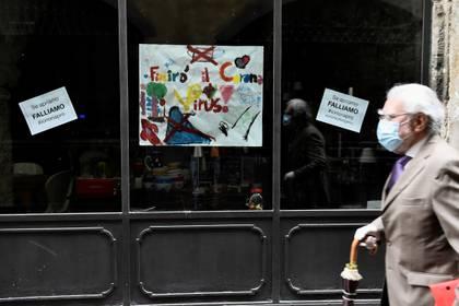 Un hombre con barbijo pasa frente a una tienda en Bérgamo, una de las ciudades más golpeadas por el coronavirus (REUTERS/Flavio Lo Scalzo/archivo)