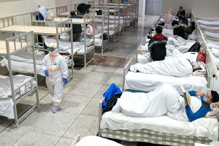 Personal sanitario con trajes protectores atiende a los pacientes del Centro Internacional de Conferencias y Exposiciones de Wuhan, que se ha convertido en un hospital improvisado para recibir a pacientes con síntomas leves causados por el nuevo coronavirus, en Wuhan, provincia de Hubei, China [5 de febrero de 2020] (China Daily vía Reuters)