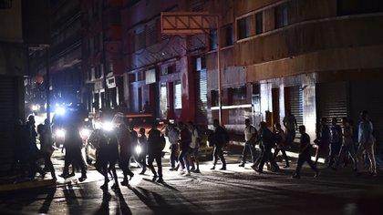 """La gente cruza una calle durante un corte de energía en Caracas el 7 de marzo de 2019. – El gobierno de Nicolás Maduro denunció un """"sabotaje"""" contra la principal represa de energía eléctrica en el país, luego de un apagón masivo que dejó a Caracas y vastas regiones de Venezuela en el oscuridad. (Foto por YURI CORTEZ / AFP)"""