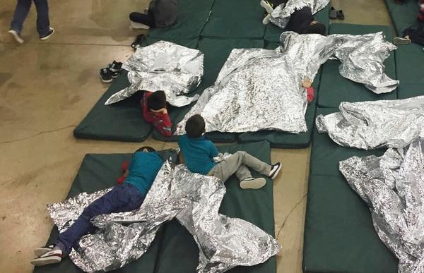 Niños detenidos por intentar entrar al país sin autorización descansan en una de las jaulas en el centro de McAllen, Texas (Oficina de Aduanas y Protección Fronteriza vía AP)