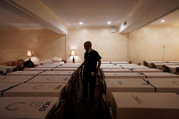 El funerario Omar Rodriguez revisa los ataúdes en su casa velatoria de Queens