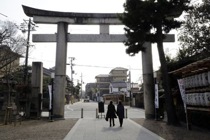 "Pedestrians walk under a ""trii"" gate at the Yasaka shrine in Kyoto, Japan. Photographer: Kosuke Okahara/Bloomberg"