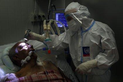 Un doctor examina los ojos de un paciente con COVID-19 (AP)