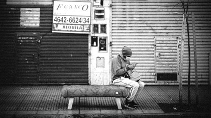Un hombre revisa su celular frente a locales comerciales cerrados en Buenos Aires (EFE/ Juan Ignacio Roncoroni)