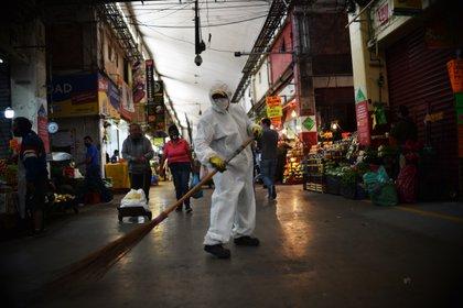 Un trabajador barre el piso en el mercado de la Central de Abastos en la Ciudad de México, el 10 de junio de 2020 (Foto de RODRIGO ARANGUA / AFP)