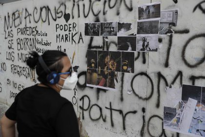 Una persona observa unas fotos e ilustraciones en uno de los muros del jir�n Quilca, el 24 de noviembre de 2020 en Lima (Per�). EFE/Paolo Aguilar