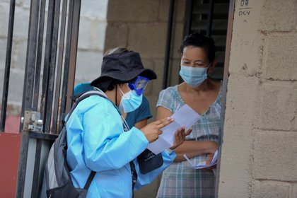 A Public Health employee, part of the Honduran Government's Anti-Covid Medical Brigades, interviews a person in search of positive cases of Covid-19, on October 30, 2020, in a neighborhood of Tegucigalpa (Honduras).  EFE / Gustavo Amador / Archive