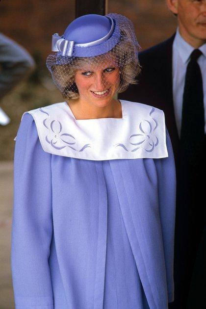 La princesa Diana Spencer en 1984 con un diseño en color lavanda con hombreras y un fascinator a tono con red